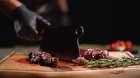 separação : Male hand in black rubber gloves separates the pieces of meat lying on the cutting board with a cutting knife. Close up. Slow motion. Stock Footage