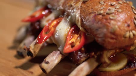 çili : Tasty sandwich with juicy beef ribs lying on the wooden board in modern restaurant close up Stok Video