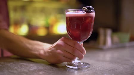 dut : Male hand puts glass with pink cocktail and mulberry on the table close up
