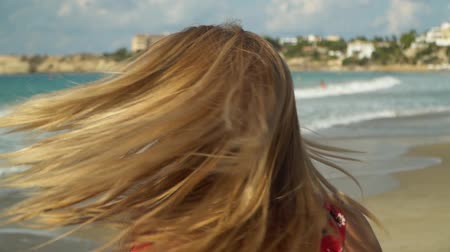 dlouhé vlasy : Young blond woman shakes her head, making her blond hair fluttering on the sea background in slow motion. Lonely girl spends time at the sea. Leisure of young lady Dostupné videozáznamy