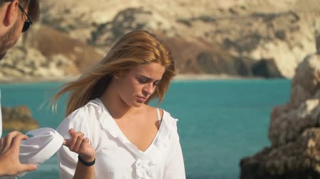 tomar : Sad blond woman standing at the sea holding white shirt. Man takes clothes from girls hand. Couple resting at the rocky beach