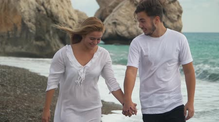 uomo alto : A happy smiling joyful couple walks along a rocky shore by the sea or ocean holding their hand. Slow motion.