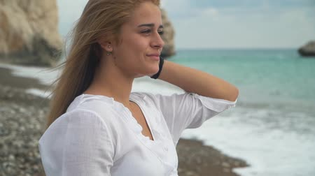 chill out : Attractive young girl with fluttering hair in the wind enjoys the wonderful weather by the sea. Close up