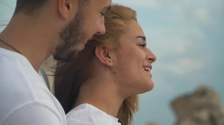 téma : Young man hug from behind a beautiful blond woman and they are happy talking
