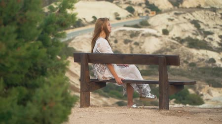 looking far away : Young beautiful woman with amazing long blond hair sitting on the bench on the high hill
