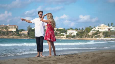 madness : Young couple standing at the rocky sea cost talking emotionally, Man and woman arguing, man makes sharp gestures. Conflict in young family