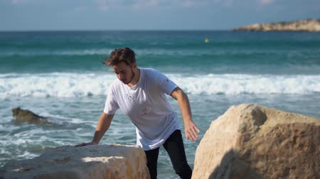 tshirt : Young handsome man climb rock near amazing sea. View is very beautiful