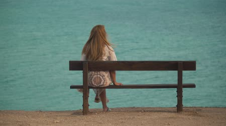 bank : Lonely girl in long white dress sitting at the bench back to camera on sea or ocean background. Laisure of blond woman at summer. Stok Video