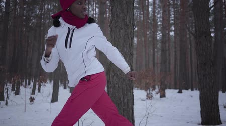inseguimento : African american woman dressed warm wearing a red hat, scarf and white jacket running through the snowy forest. The girl constantly looks back running away from the pursuer. Slow motion.