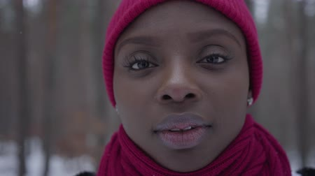 individuální : Close-up portrait of an African American girl dressed warm wearing a red hat and a red scarf standing in a snowy forest. Real people series.