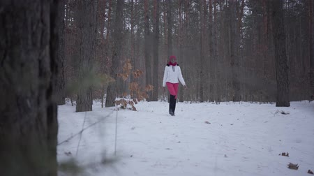 stop motion : African american girl dressed warm wearing a red hat, scarf and white jacket walking in winter forest. Concept of outdoor recreation