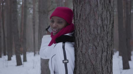 winter day : African american girl throws a handful of snow standing in winter forest and looking from behind the tree. Beautiful girl in warm jacket have fun outdoors. Concept of outdoor recreation