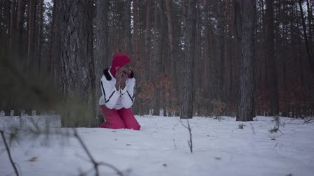 perseguição : African american girl calling by cell phone sitting behind tree in winter forest. Beautiful woman in white jacket gets up and start to run, she is scared. Woman trying to call help