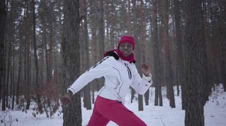 dát : Scared African american pretty woman dressed warm wearing a red hat, scarf and white jacket running through the snowy forest. The girl constantly looks back running away from the pursuer. Slow motion.