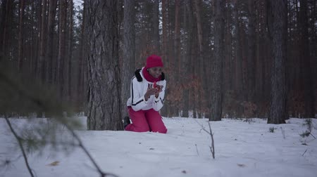 pánik : Scared African american girl calling by cell phone sitting behind tree in winter forest. Woman trying to call help