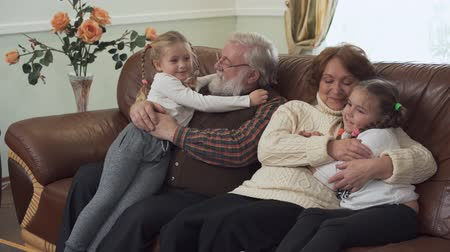 kin : Happy gray-haired bearded grandfather and sweet grandmother hugging and kissing their small funny granddaughters