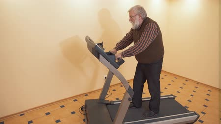 treadmill : An adult gray-haired bearded man dressed in dark jeans, a red vein and a plaid shirt is engaged on a simulator. Grandpa walks on a treadmill at home.