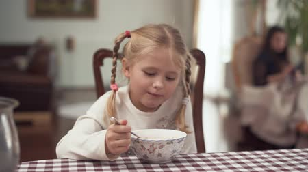 przedszkolak : Cute blond girl with pigtails eating borshch sitting at the table in modern kitchen on blurred background. Little girl having her breakfast