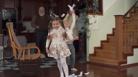 wicked : Two funny active granddaughters indulge, run and throw pieces of paper on the floor on the background of shocked grandparents which cant calm them down. Slow motion Stock Footage