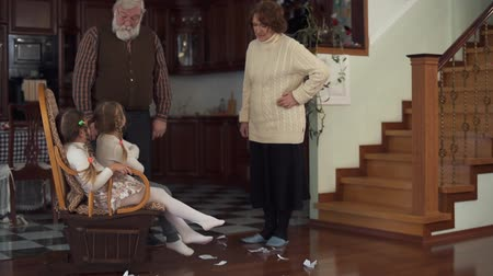 wicked : Two funny active granddaughters indulged, and thrown pieces of paper on the floor and their grandparents cursing them and telling to clean everything . Slow motion