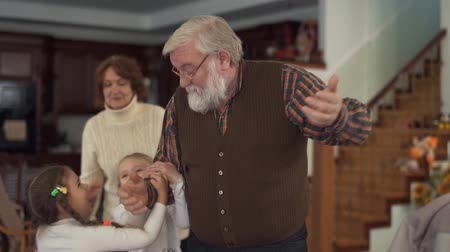 run down : Old man playing with his grandkids in big living room close up. Grandfather stands with hands up, two girls catching his hands and pulling down. Kids having fun in grandfathers house