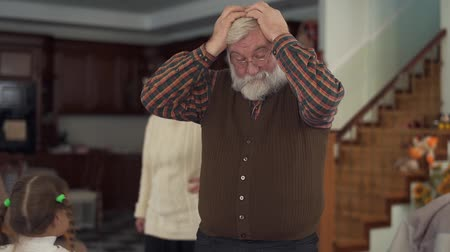 wicked : Grandparents grabs their head becouse cant reassure their naughty running granddaughters, very are angry and tired. Slow motion Stock Footage