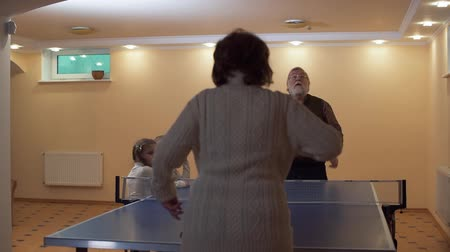 nagypapa : Grandfather and grandmother play table tennis, two small girls watching the game. Senior woman gives a pass to a man, he clumsily beats off the ball. Leisure of happy family