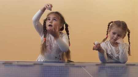 pigtail : Two pretty little girls with braided pigtails playing with table tennis balls. Leisure of happy sisters. Slow motion.