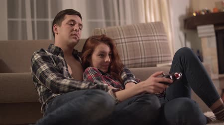 evli : Young happy couple lie down on the floor and play video games Stok Video