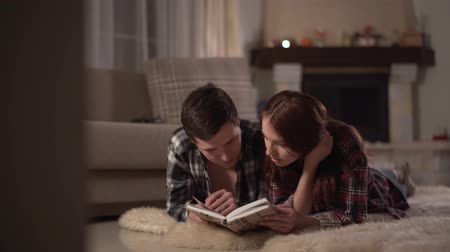 acalmar : Young happy man and woman lie down on fluffy curpet in the living room with fire place and reading a book. Pastime of a young couple in love. Leisure of young family. Stock Footage