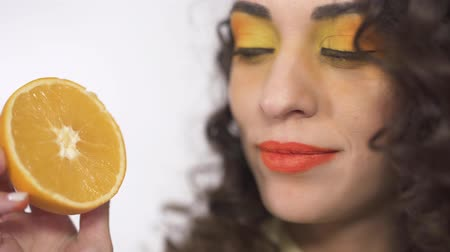 seduzir : Close up portrait of young curly girl with bright make up licking ripe juicy piece of orange with pleasure.