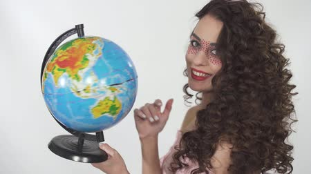ruj : Portrait young beautiful curly girl with creative make up twisting globe with fun and pretty smile. Girl stops the globe with a finger choosing a country. Stok Video