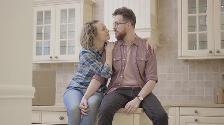 belongings : Bearded man and pretty woman sitting on the table in kitchen. Woman hugs husband and leans on his shoulder, smiling. Married couple have a fun at home. Camera moves left behind wall