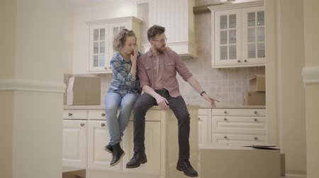 souhlasit : Bearded man and pretty woman sitting on the table in kitchen of new apartment. Family discuss plans about new flat. Married couple moves into a new home. Camera moves to the right