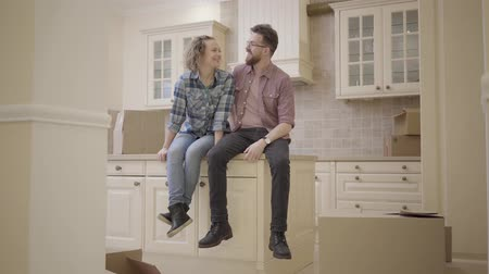 belongings : Handsome bearded man and cute woman sitting on the table in kitchen in new apartment. Family discuss plans about new flat. Married couple moves into a new home.