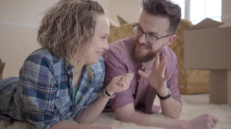 deslocalização : Young family lying on fluffy carpet close up with boxes in the background. Man showing key to woman, she stretches out hand and takes it, smiling. Married couple moves into a new home Stock Footage