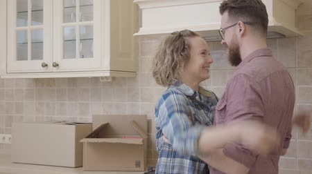 coisas : Joyful young family embracing in the kitchen in their new home. Happy couple moving to a new apartment. Stock Footage