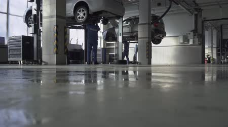 ajustando : Indoor big pasted safety car service workshop with modern equipment on the middle of hard working day Vídeos