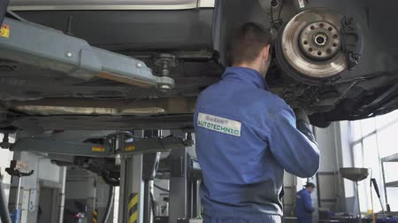 csavarkulcs : Proffesional car maintenance at service station. Car service, repair, maintenance and people concept - mechanic man working at workshop. Car service employee repairing a vehicle.