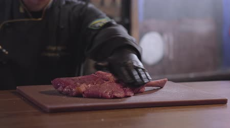 makbuz : Chef pours piece of meat with bone with syrup on both sides close up. Cook in black robe and rubber gloves cooking dish. Preparing food in restaurant
