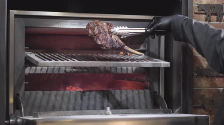карри : Chef in black gloves opening the oven grill, in which are preparing fried rib to flip it to the other side. Close up