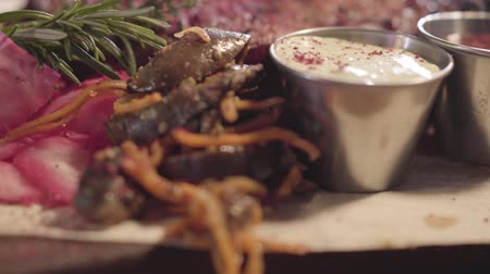 mouth watering : On the table in the restaurant are ready to serve beautifully served meat, kelp, sauces, ginger, rosemary and vegetables. Close up Stock Footage