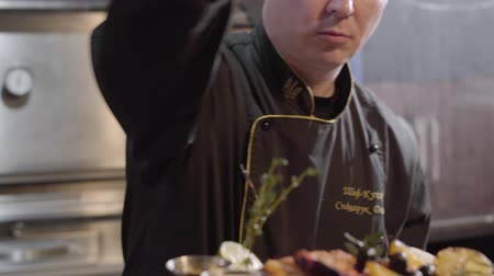 biber : Portrait of chef in black gloves serving and salt on a desk grilled fish, sliced pieces of bell pepper, olives and lime. Close up Stok Video