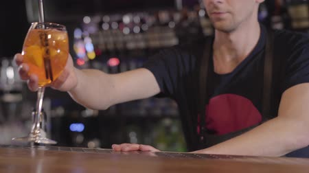 паб : Barman puts two black straws in high cocktail glass with ice cubes and orange close up. Young man prepared tasty cocktail and puts it on bar counter