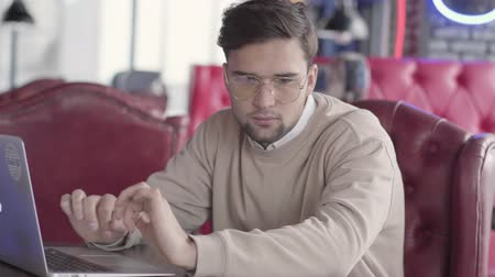 netbook : Handsome man working with laptop in modern cafe close up. Stylish confident businessman moves his body in rhythm of music. Positive freelancer working on project