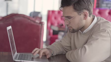 netbook : Handsome man working with laptop in modern cafe close up. Stylish confident businessman thinking about solving problem. Serious freelancer working on project. Camera moves to right
