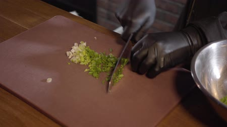 mouth watering : A cook in black rubber chef gloves cuts finely fresh onions on a cutting board and throws it into an iron bowl on a cutting board in a restaurant kitchen. The concept of cooking.