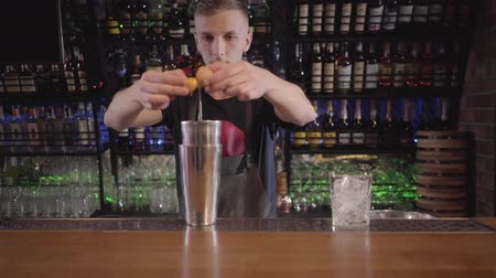 separação : Professional bartender breaks the egg on the shaker and separates the white from the yolk close up. Figure of man is blurred. Barman making healthy cocktail in the bar Stock Footage