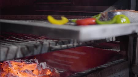 geschafft : Hand of cook in black glove puts piece of salmon with vegetables in oven using metal tool close up. The chef push fresh juicy fish inside grill oven. Preparing food in a modern restaurant. Slow motion