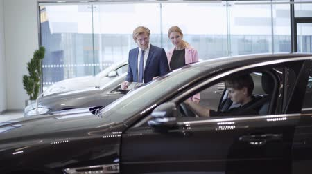 продавщица : Confident woman with short hair sitting in the car in front of smiling businessman and saleswoman discussind buying automobile. Man choosing automobile for his wife in motor show